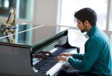 Gabe Daniels, MS2, volunteers with UF Health Shands in Medicine, playing piano in the south tower atrium.